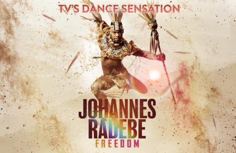 Johannes Radebe in African Dance costume jumping in the air