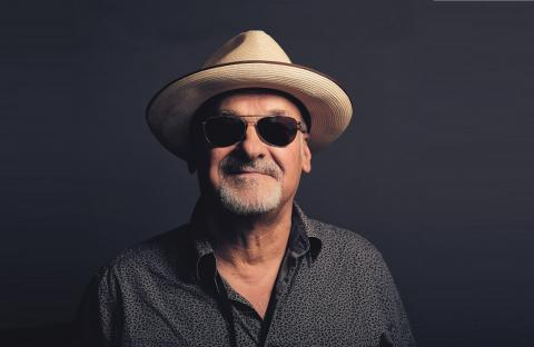 Paul Carrack in dark open necked shirt and shades with large brimmed hat on