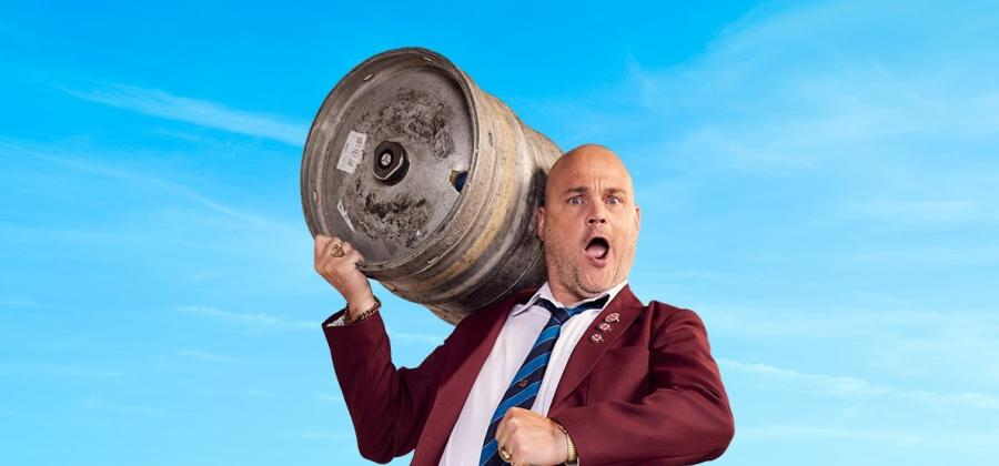 Al Murray with a beer barrel on his shoulder in burgandy jacket and white shirt.