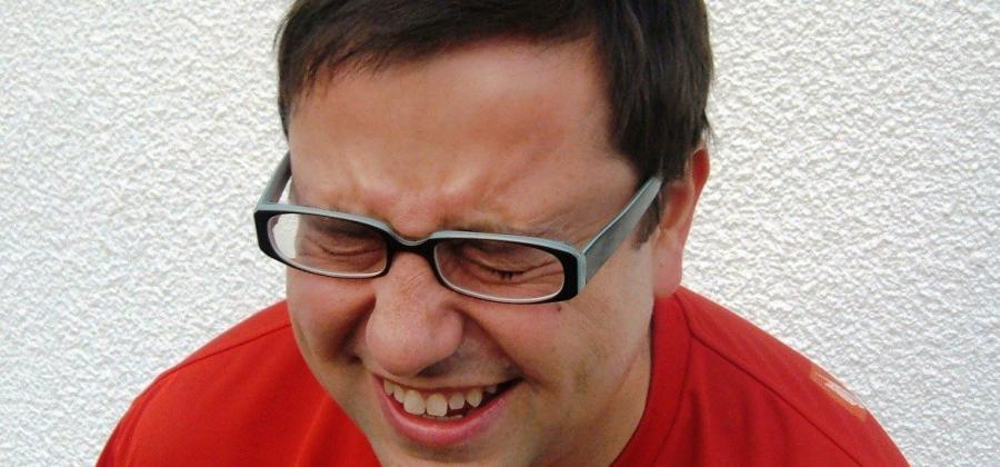 Bespectacled man in red top laughing