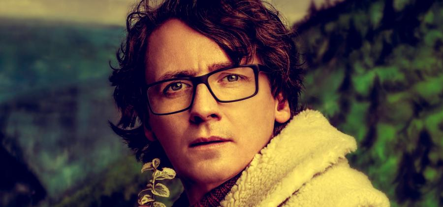 Ed Byrne in a flying jacket holding a plant