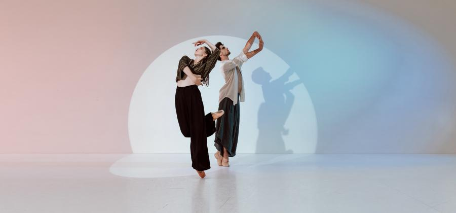 Two Dancers in black trousers strike a contemporary pose while facing away from one another