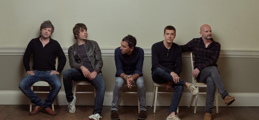 The band all seated, side by side against a cream wall. Photo by Tom Oxley,
